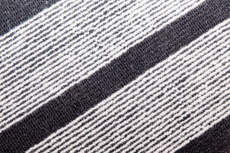 rug texture: Wool rustic rug with  white and black stripes, texture background.