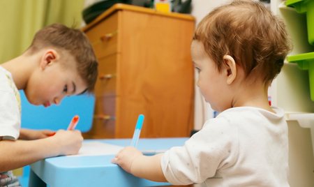 copying: younger brother is watching and copying actions elder brother (drawing in the nursery)
