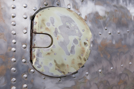 aluminum airplane: manhole cover in the casing of the old military plane Stock Photo