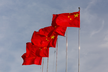 flagpoles: Chinese flags on flagpoles in a row Stock Photo