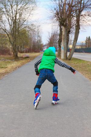 ni�o en patines: ni�o de conducci�n europeo sobre patines de ruedas en el comienzo de la primavera