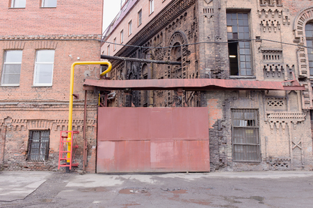 back gate: Facade of a pink building wall with sliding metal door.