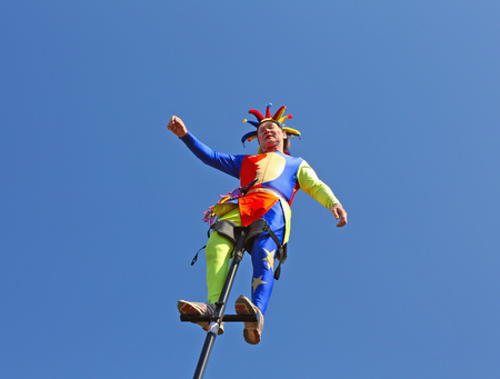 clowning: St. Petersburg, Russia-16 April 2016: Street circus clown on a mast on a background of blue sky.