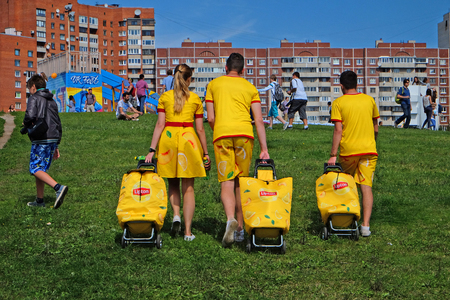 Saint Petersburg, Russia - July 17, 2016: three street promoter LIPTON products move through crowded Park Editorial