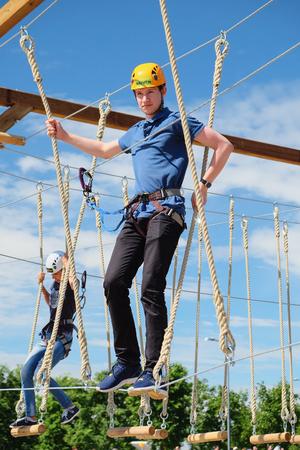 tallness: Saint Petersburg, Russia - July 17, 2016: man walking on a rope ladder, a rope Park Editorial