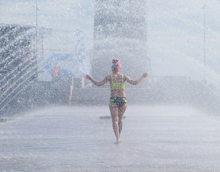 nice body: woman with nice body is cooled under the jets of the fountain Stock Photo