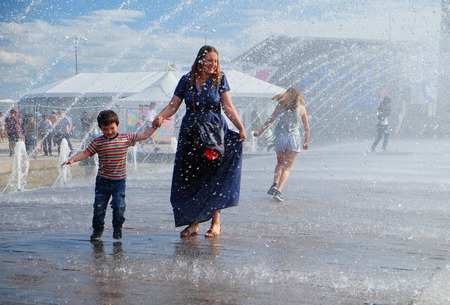 heat wave: St. Petersburg, Russia - July 17, 2016: a mother and her child walks under the jets of the fountain during the heat wave