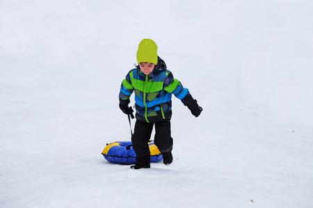 to go sledding: European boy tugs at the inflatable slide (snow) sledge