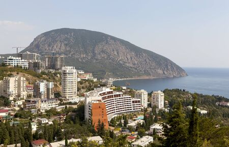 Rocky Beach with a protruding rock domes of churches and residential buildings located among different vegetation. The settlement Gurzuf and Bear Mountain Au-Dag . Crimea. View from Bolgatura Mountains in Gurzuf. Located in the northern part of the city G Stock Photo