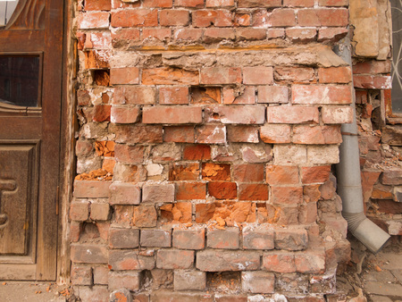requiring: close-up of an old brick building requiring repair