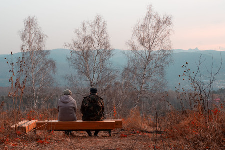 man and woman sitting on a bench in the park in the fall Stock Photo