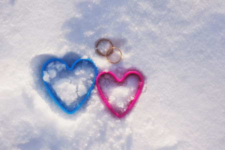 the image of two of hearts in snow with wedding rings.