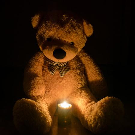 jouet, ours, assis dans le noir, bougie, tristesse.