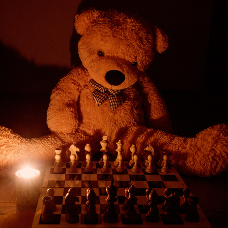 toy bear sitting at the chessboard, lit a candle.