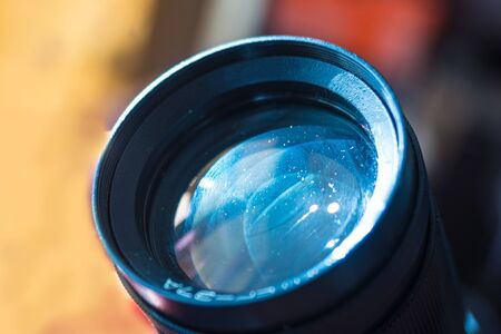 Close up camera lens with light reflection.