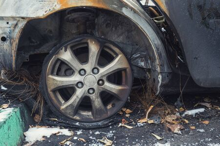car after deliberate arson. destroyed car after the fire is on the street.