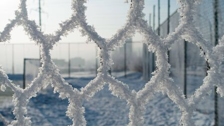 Frozen fence made of metal mesh covered with snowy hoarfrost, winter day.