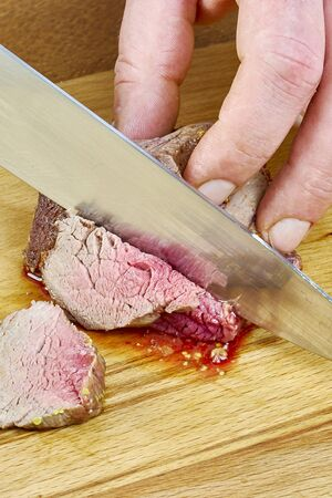 provocative food: Chef cuts grilled meat on the board with a full series of blood recipe cooking