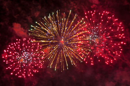 The simultaneous colorful explosion of three salute salvoes in the night sky. Fireworks out of focus. Holiday concept.