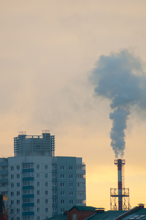 Thick smoke rises from the chimney high above the city against the backdrop of an orange sky.  City at sunrise.  City, air and environmental pollution. Climate Change Theme. View of pipe with smoke and residential apartment buildings. Stock Photo