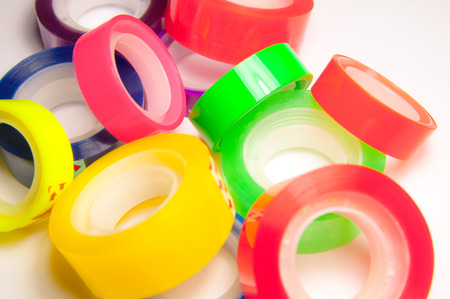 Group of colorful scotch tape adhesive. Many rolling tapes.
