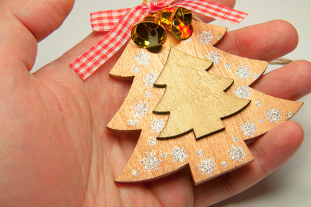 Flat handmade toy christmas tree from wood  in the mans hand