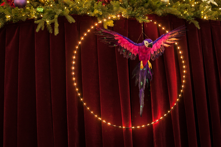 Color parrot toy in a large bright LED circle on the background of burgundy screen. Above the screen, green branches of spruce with toys and a bright garland.