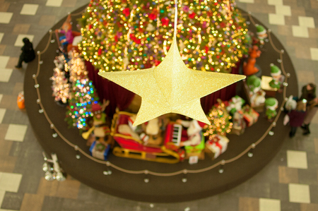 Golden Christmas star in the center of the frame. Blurred background of Christmas decorations in the mall. Visible blurred silhouettes of people. Christmas tree in the middle of the shopping center