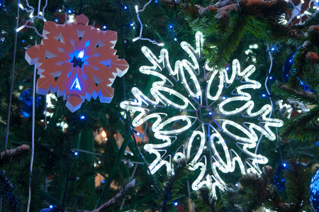 Bright glowing big LED and small foam snowflakes  on Christmas tree at night. Beautiful christmas decoration in the city. Christmas and new year holiday concept.
