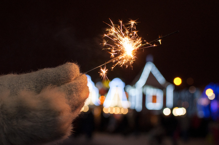Female hand in a warm gray mitten holding a burning Bengal light on Christmas background in the form of luminous contours of  colorful decorated houses. Gold beautiful sparkles from Bengal fire.