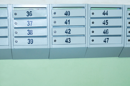 Metal gray mailboxes on a green wall with numbers from 36 till 47 on them. Mailboxes of an apartment building. Mailboxes with locks. Stock Photo