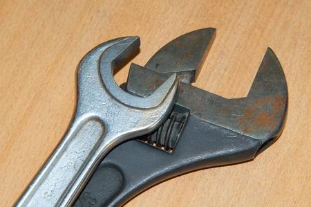 Adjustable old wrench on wooden table. Silver wrench and black adjustable wrench.