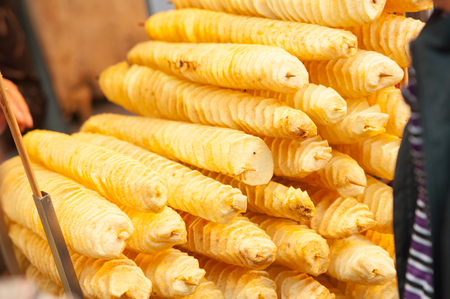 Stack of golden spiral potato chips on on a wooden sticks. Street market in Xian. Unhealthy fried food on the street. Street fast food in China. Stock Photo