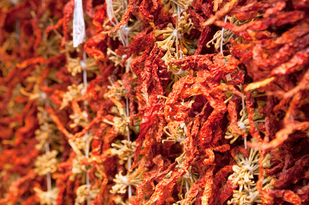 A lot of dry hot red paprika pods are hung vertically on threads. Street market in Xian.  Food on the street in China. Spicy seasoning for cooking delicious food. Selective focus.