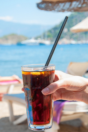 Young woman hand holding a transparent glass with drops of water of cola with ice at the beach in sunny day. Blurred chaise lounges, sea and mountains in the background. Lady rests on vacation days.