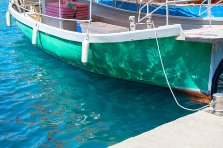 Green boat for tourists  transportation near the pier, tied by a rope. A stern with water surface reflections. Vacation in Turkey, Marmaris, Aegean sea.
