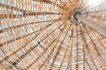 Bottom view on a wicker beach umbrella. Woven wooden beach umbrella against the blue sky with bright sun. Holiday resort concept.