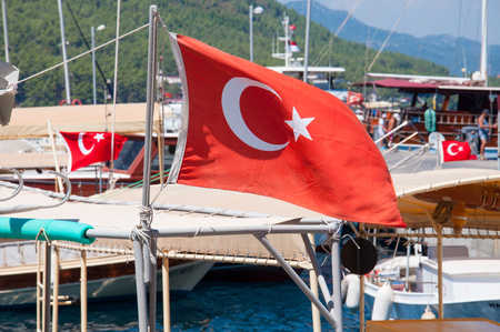 Red National Flags of Turkey with a half month and a star waiving on the wind on Mediterranean Sea in (Marmaris), Turkey.