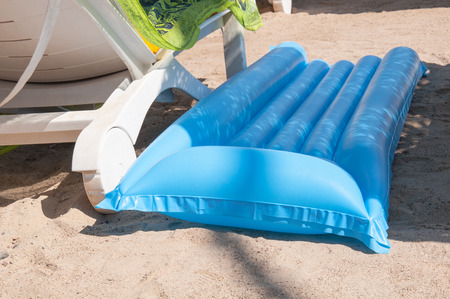 Inflated blue air mattress on the beach with shadow from a wicker beach umbrella near white plastic chaise in a sunny day. Inflatable mattress for relax and sunbathing on the waves.
