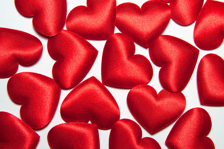 Background of many bright red silk small decorative hearts with a short distance from each other. Decorative hearts for Valentines day or Wedding.
