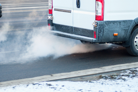 Pollution of the atmosphere by gas from the exhaust pipe of a white van in motion in the city. Combustion fumes coming out of back car in winter time. Air pollution concept. Motion blur.