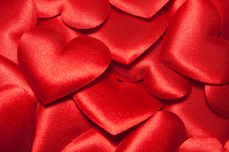 Many big colorful red silk hearts.  Vlentines day background with red hearts.