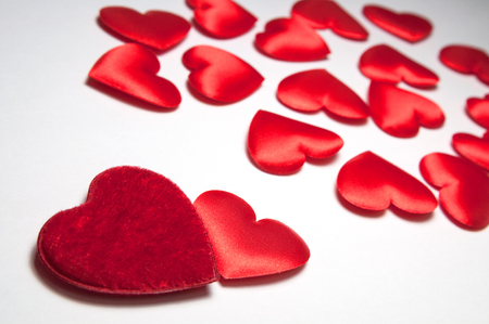 Two red hearts are near and many small blurred hearts. The concept of two loving people who have found each other among hundreds of other lonely hearts. Decorative hearts for Valentines day.