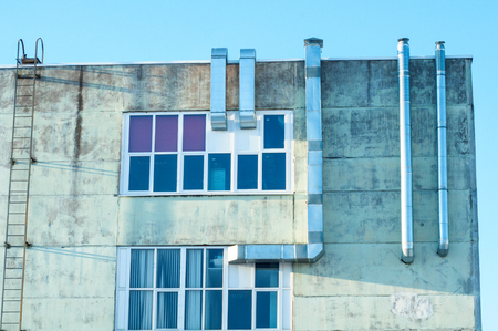Facade of an old industrial building with metal aluminum ventilation exhaust pipes, fire escape ladder to the roof and modern large plastic windows.