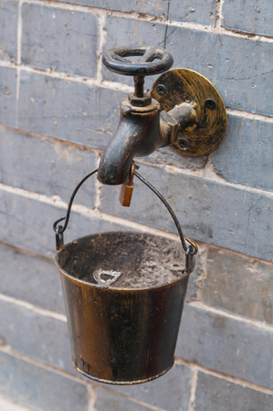 Decorative small metallic bucket hanging on the water tap with Faucet. Bucket with handle used as an ashtray. Old water tap attached to a gray brick wall.