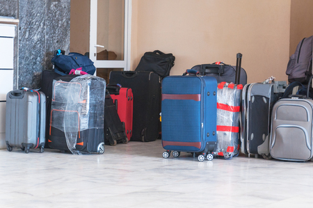 Many different suitcases and bags are in a hotel lobby of the waiting room. Check into a hotel. The concept of travel. Stock Photo