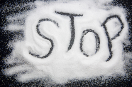 Word STOP written in salt. Medical concept antihypertensive campaign, harm to health.