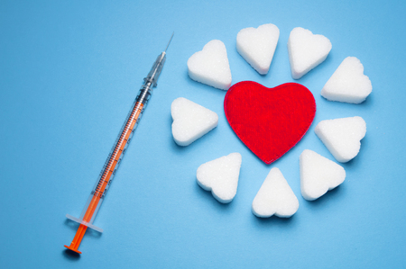 Insulin injection syringe near heart shaped sugar and red heart on blue background. Pieces of white sugar lie around a red heart. Diabetes and medicine concept. Stock Photo