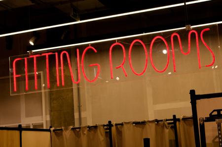Resplandeciente texto rojo HABITACIONES en una tienda de ropa moderna. Texto de neón en el letrero. La inscripción que invita a los visitantes a probarse su ropa favorita antes de comprarla.