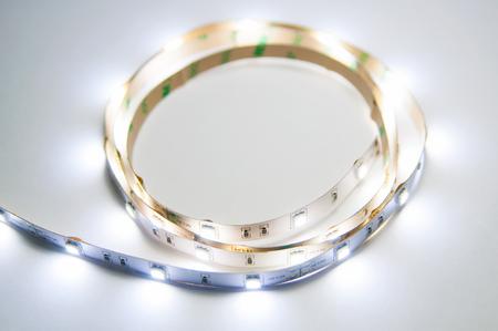 Modern glowing white twisted LED strip. Diodes emit warm white light. Stock Photo